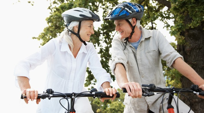 happy senior couple in helmets riding bikes