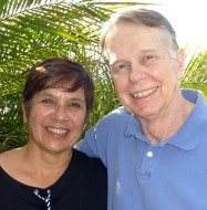 headshot of Bryant Wieneke and his wife outside in front of palms