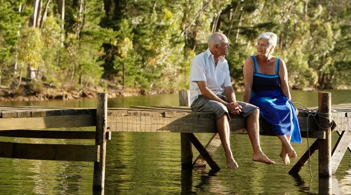 baby boomer couple sit on dock at lake