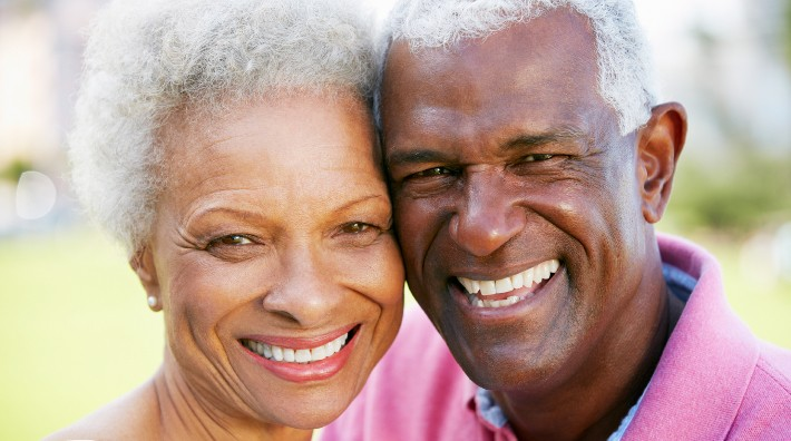 a happy African American couple with heads together