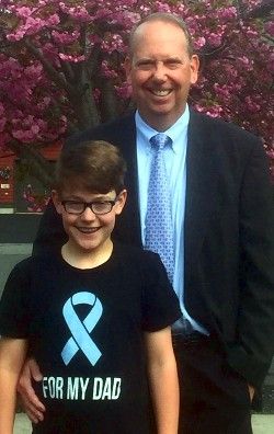 prostate cancer survivor, Brian Glennon standing outside with his son