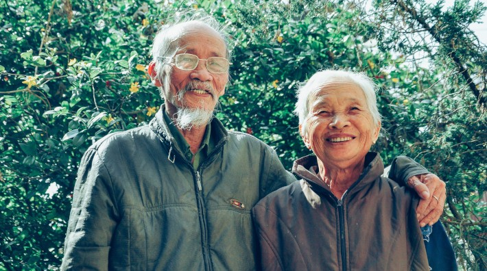 happy elderly Asian couple standing outside in front of greenery
