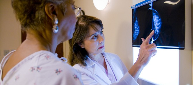 doctor goes over mammogram results with patient in exam room