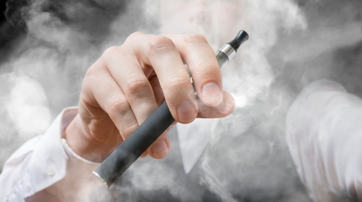 closeo up of e-cigarette in man's hand with smoke all around