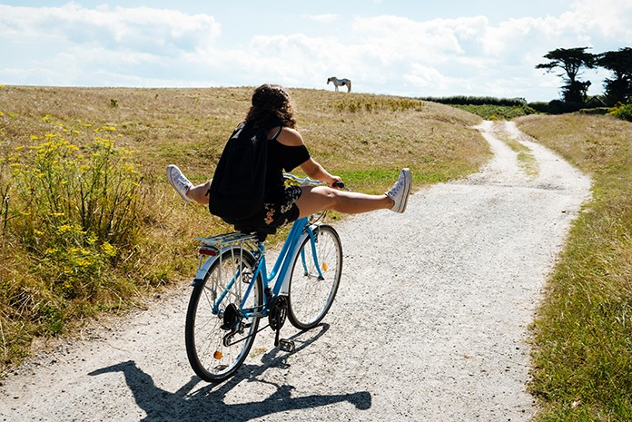 Girl on bike with feet stretched out on dirt lane facing away