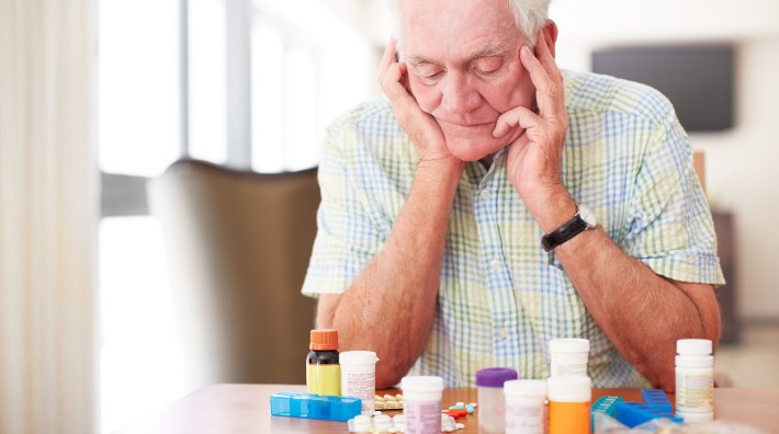 worried senior man looks at a collection of his daily medications