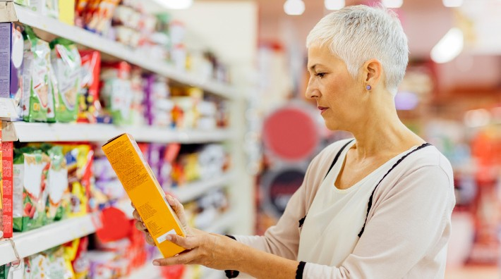 woman reads package label of item in grocery store