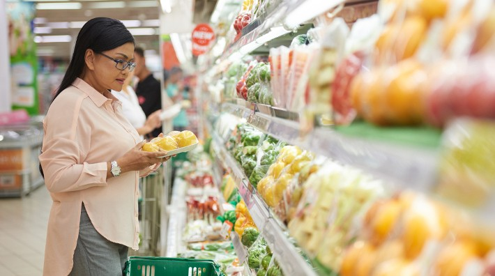 woman looking at pre-packaged fruit in grocery store
