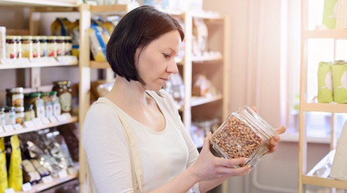 woman looking at beans in a container in the grocery store