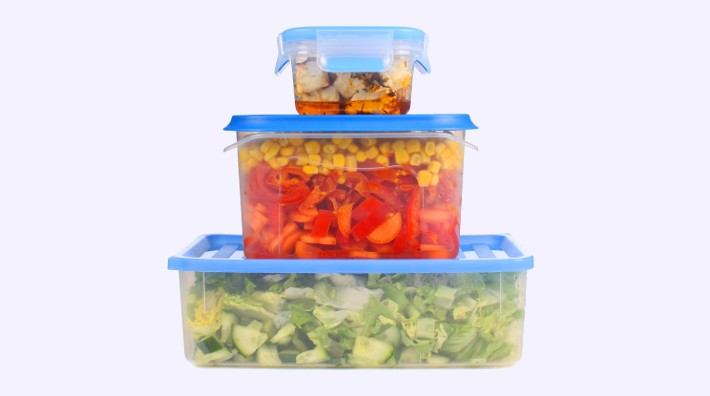 a stack of plastic containers with left-over food in them