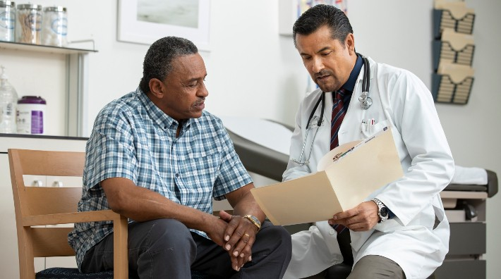 doctor goes over a chart with a male patient in exam room