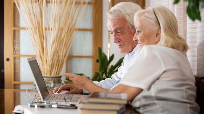 Smiling Senior Couple Working on Laptop Computer