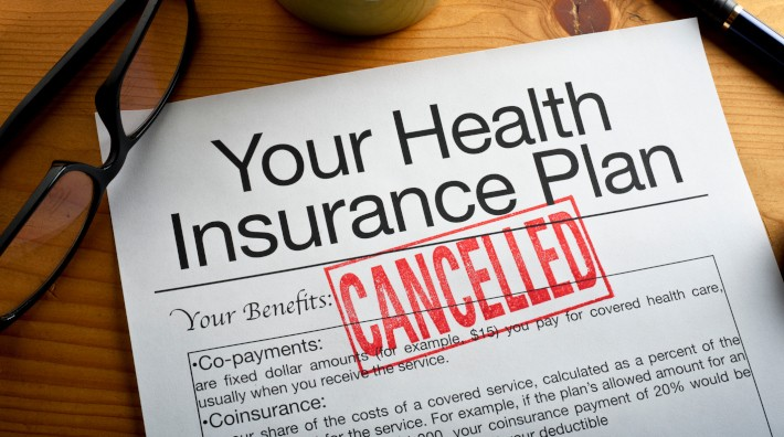 "close up of health insurance plan with the word ""Cancelled"" stamped on it in red"