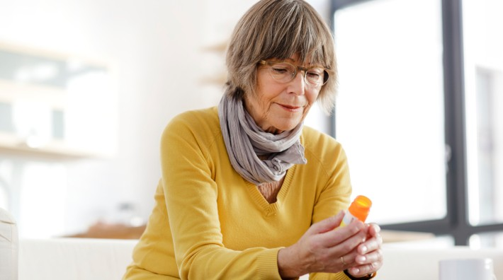 woman sitting on couch looking at the label on her prescription bottle