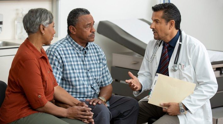 mature couple speaking with doctor in exam room