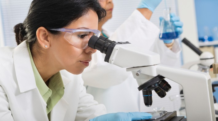 researcher looking through microscope in lab