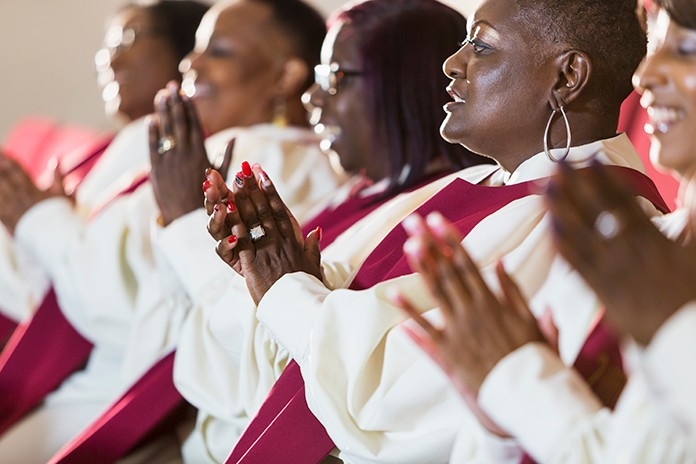 side view of Black women in red choir robes clapping