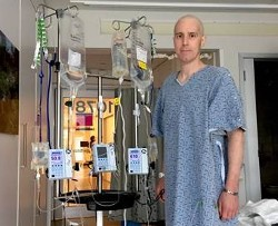 Jeremiah Ray standing in his hospital room connected to iv's