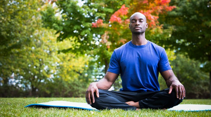 young black man wearing athletic wear sitting in the park meditating