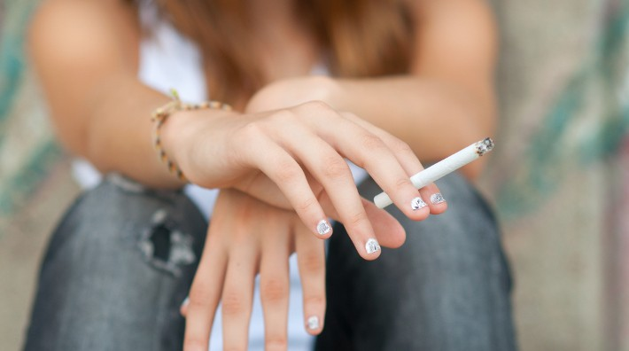 closeup of a teen girl's hand holding a lit cigarette