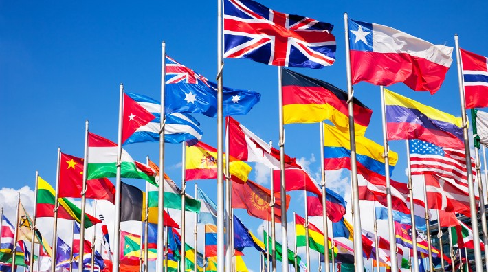 flags from many nations on flag poles, blowing in the wind against an blue sky