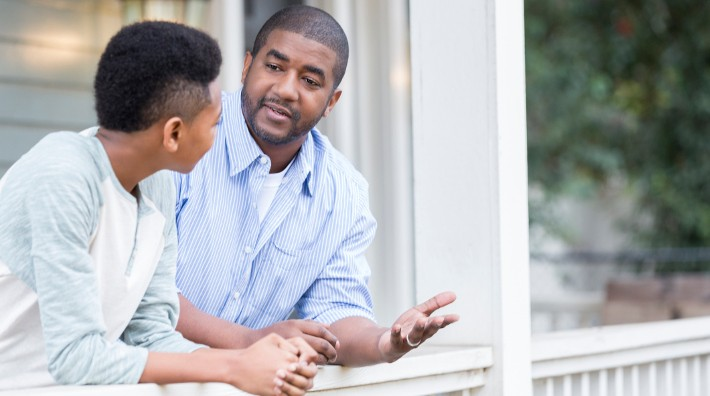 father and son having discussion on porch
