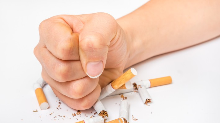female fist crushes pile of loose cigarettes