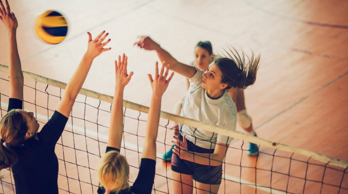 Young women playing volleyball inside gym