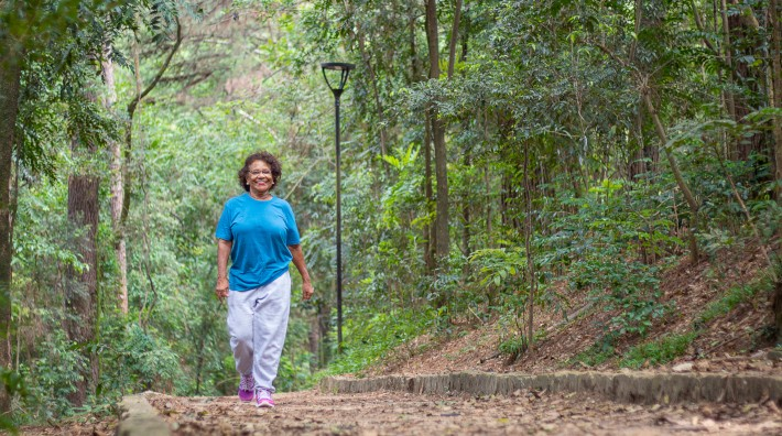 happy woman walks outside in wooded area
