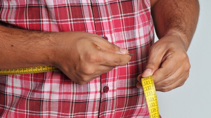 large man measuring his waist with a tape measure