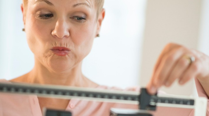 a woman makes a face as she weighs herself on an upright scale