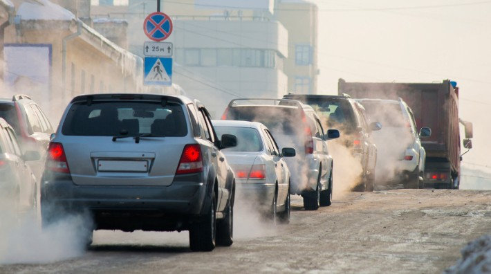 traffic jam on city streets with exhaust fumes coming from cars