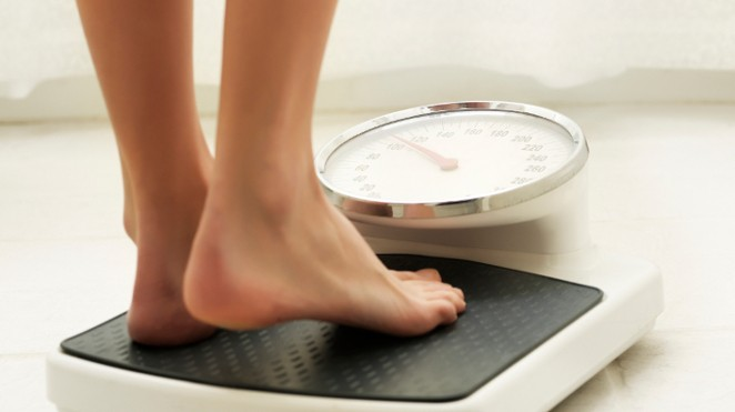 close up of woman's feet stepping onto a bathroom scale