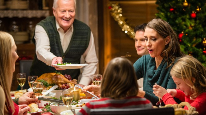grandfather serves carved turkey to his family at Christmas dinner table