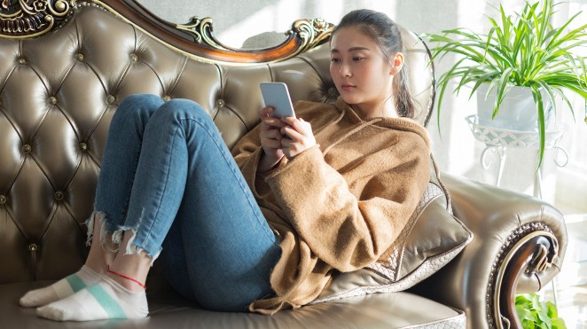 young woman sitting on a couch looking at her phone