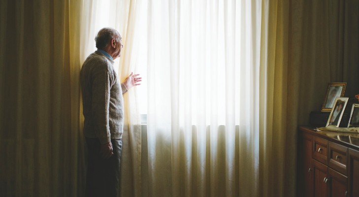 lone senior man looks out of his window