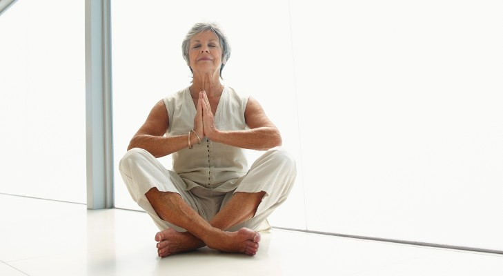 senior woman does yoga in white room
