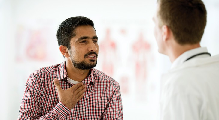 man talking to his doctor in the exam room